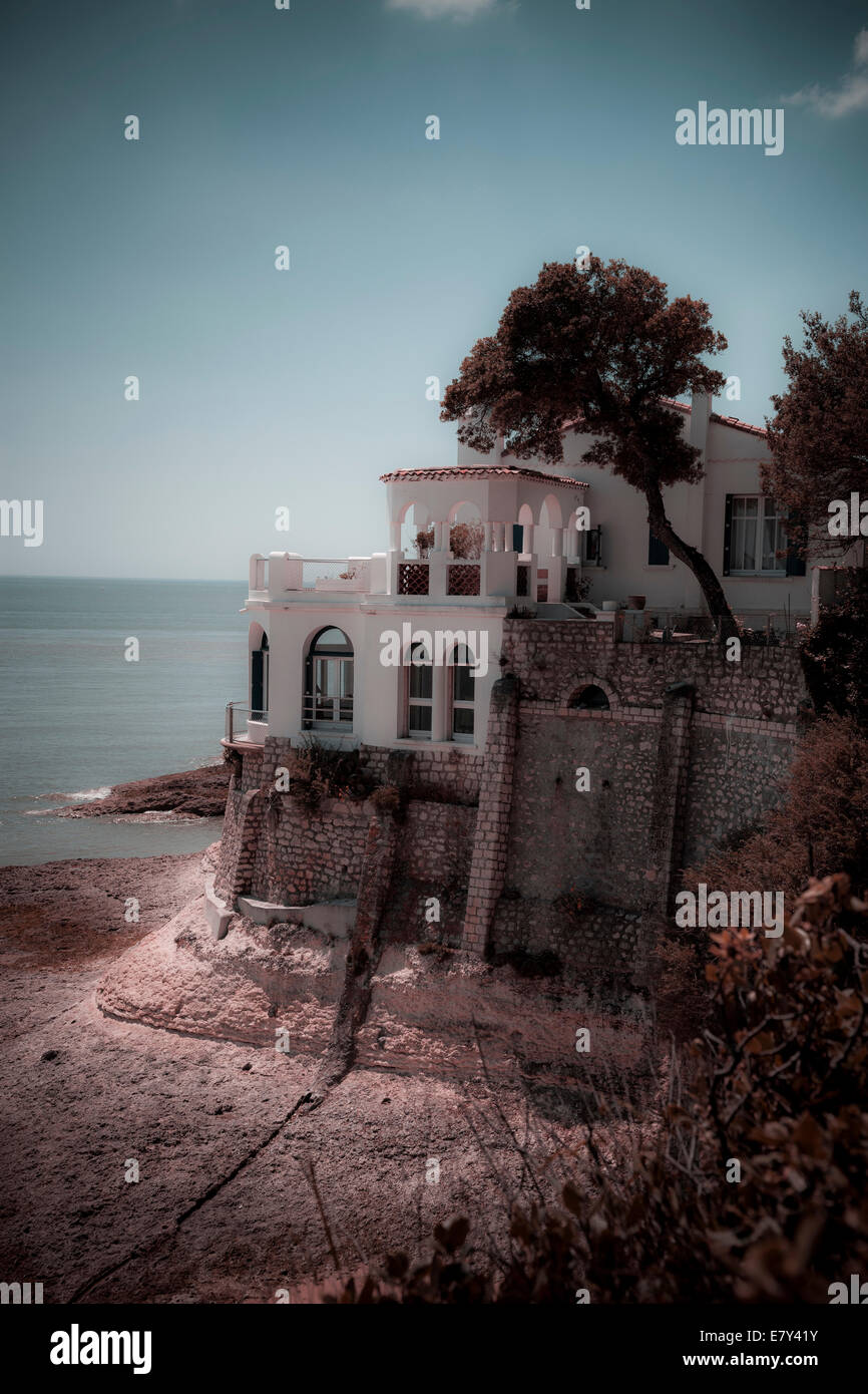 Single imposing house overlooks the calcareous rocks and sea of the Charente Maritime France instagram treatment. - Stock Image