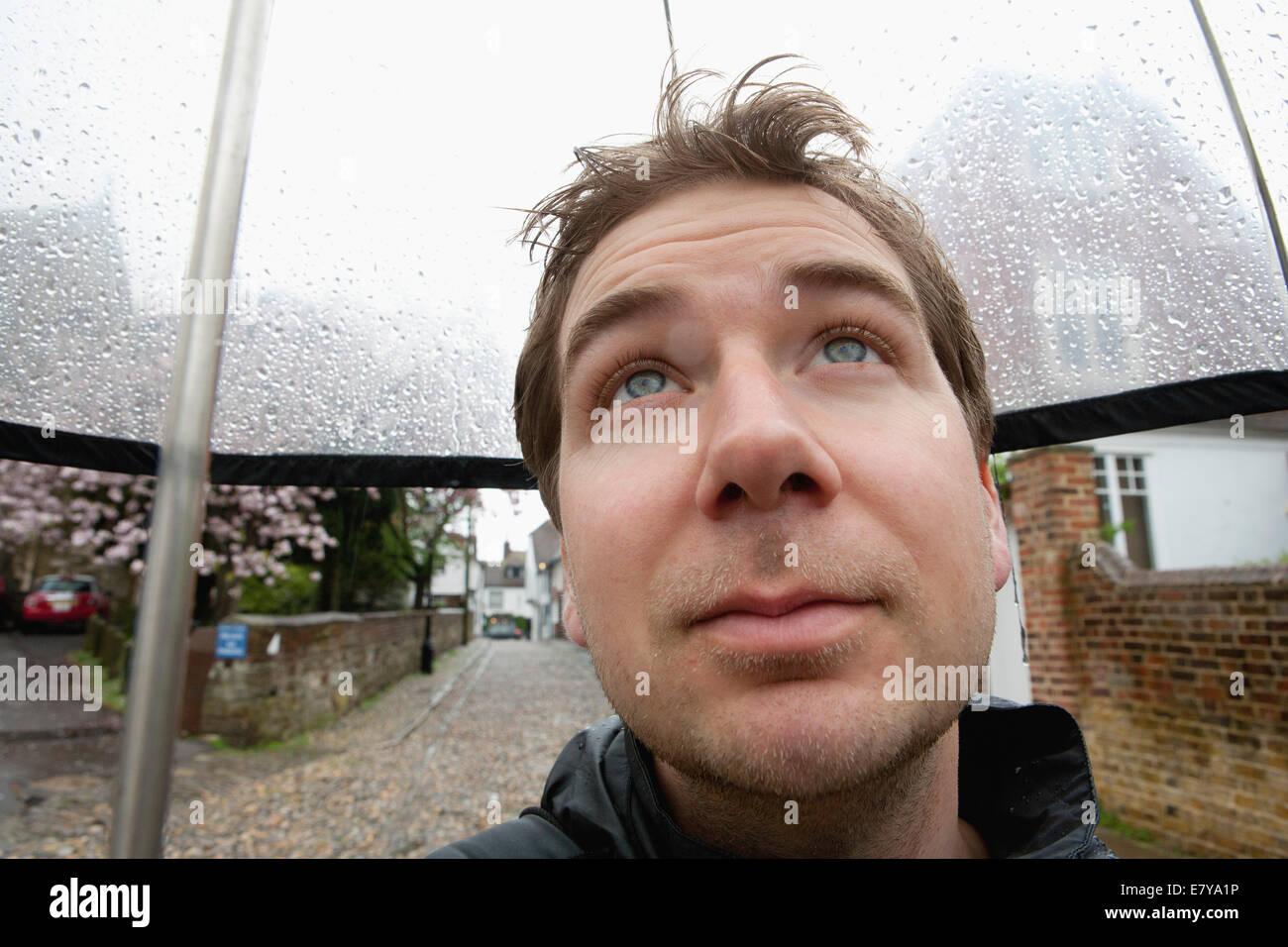 MAN SHELTERING UNDER UMBRELLA - Stock Image