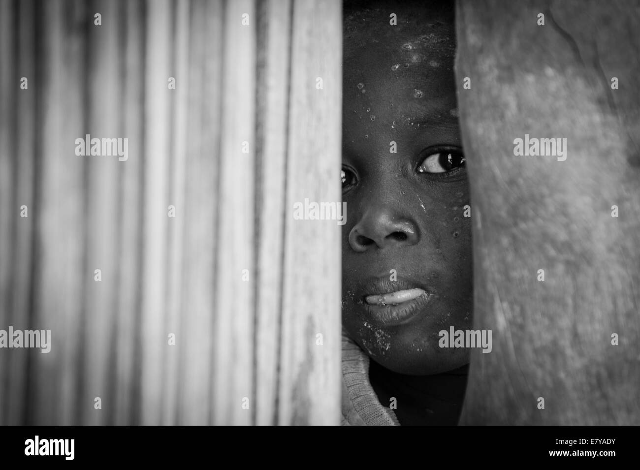African rural village child looking out of his hut - Stock Image