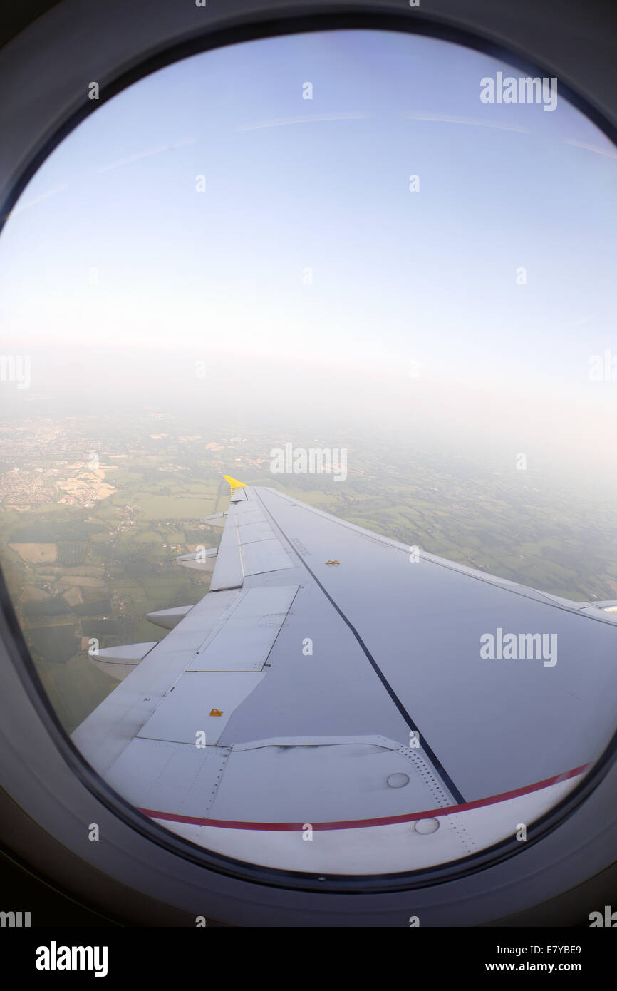 Aeroplane window and wing of aircraft. - Stock Image