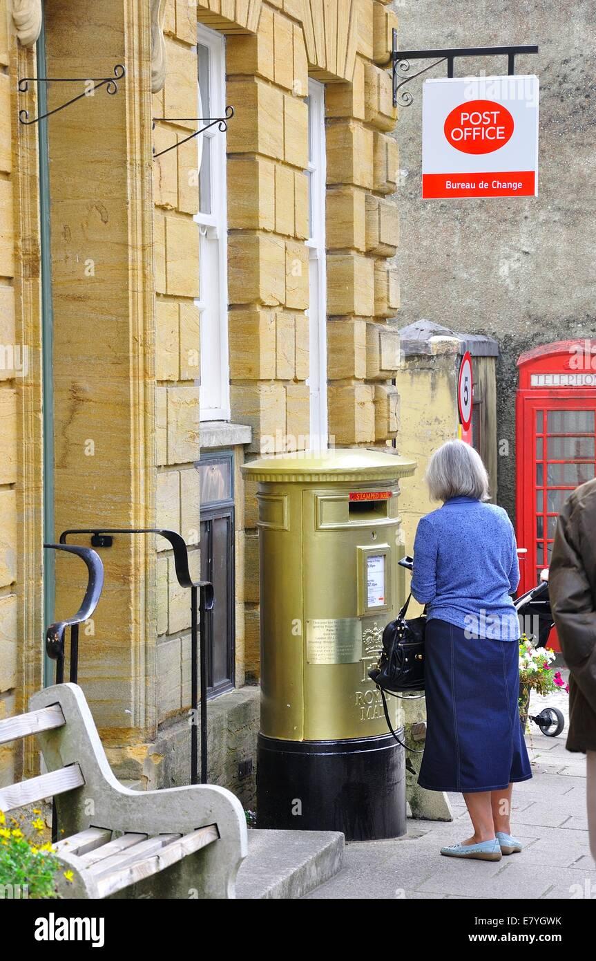 Sherbourne, Dorset. 2012 Olympic Games commemorative gold post box in honour of gold medal winner Peter Wilson - Stock Image