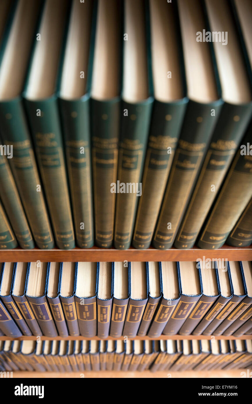 Bookshelf in library with many books. Shallow dof. - Stock Image
