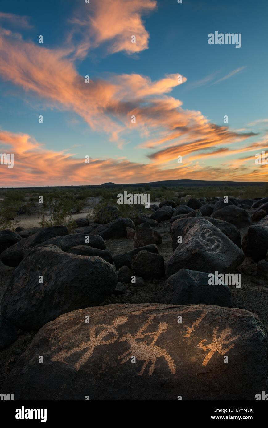 Native rock carvings beneath a colorful sunset near Gila Bend, Arizona. - Stock Image