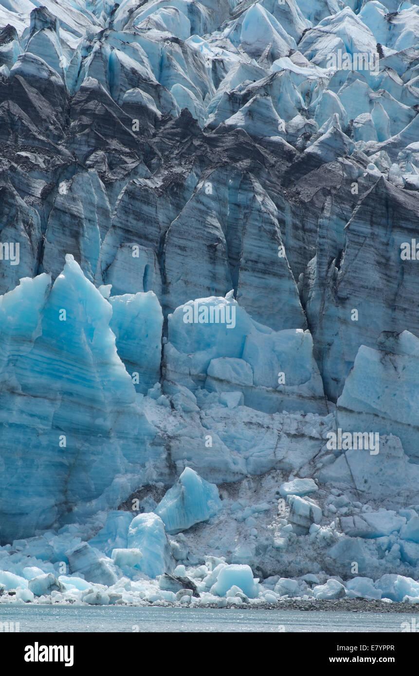 A vertical slice of the deep blue Johns Hopkins Glacier in Glacier Bay, Alaska. - Stock Image