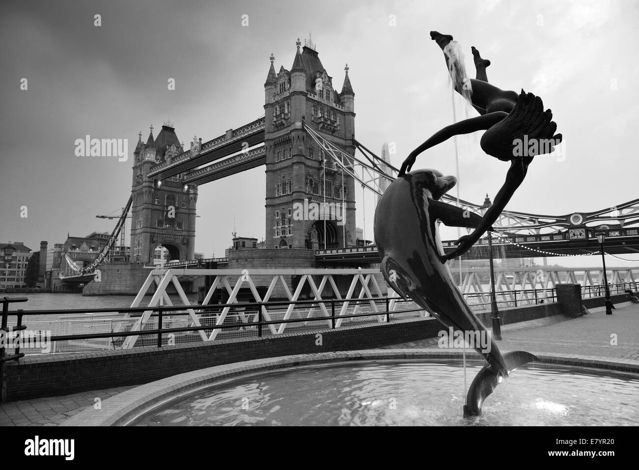 Tower Bridge and statue of a girl playing with dolphin in St Katharine docks in London. - Stock Image
