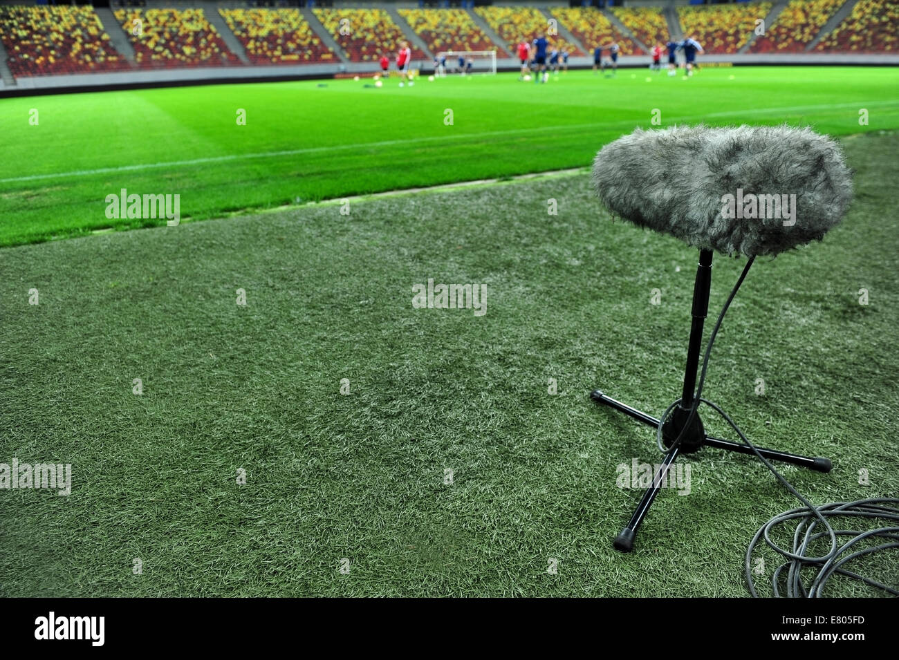 Professional sport microphone on a football field with players training in the background - Stock Image