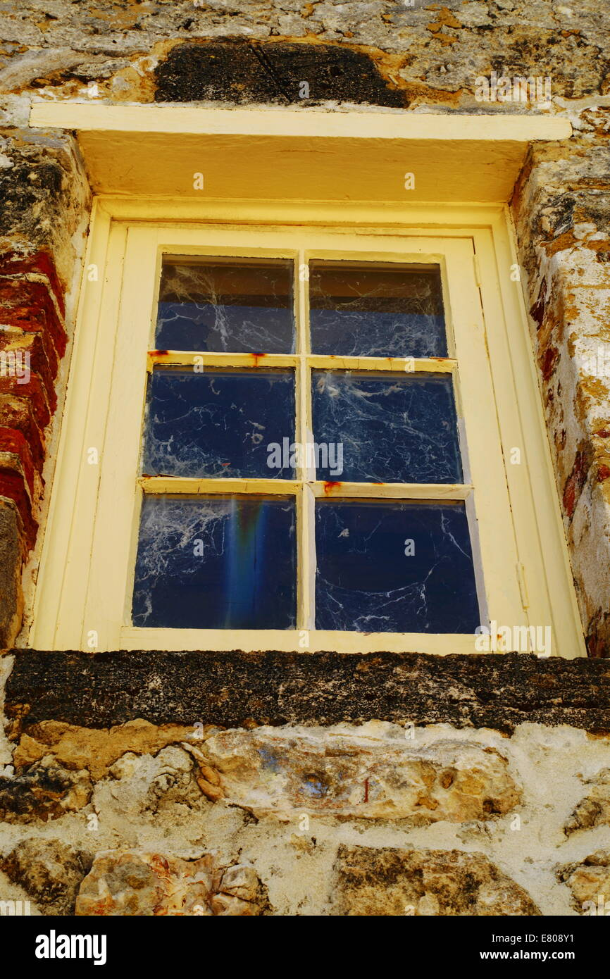 An old window thick with spider webs, set among a limestone wall at The Roundhouse (a former jail) in Fremantle, - Stock Image