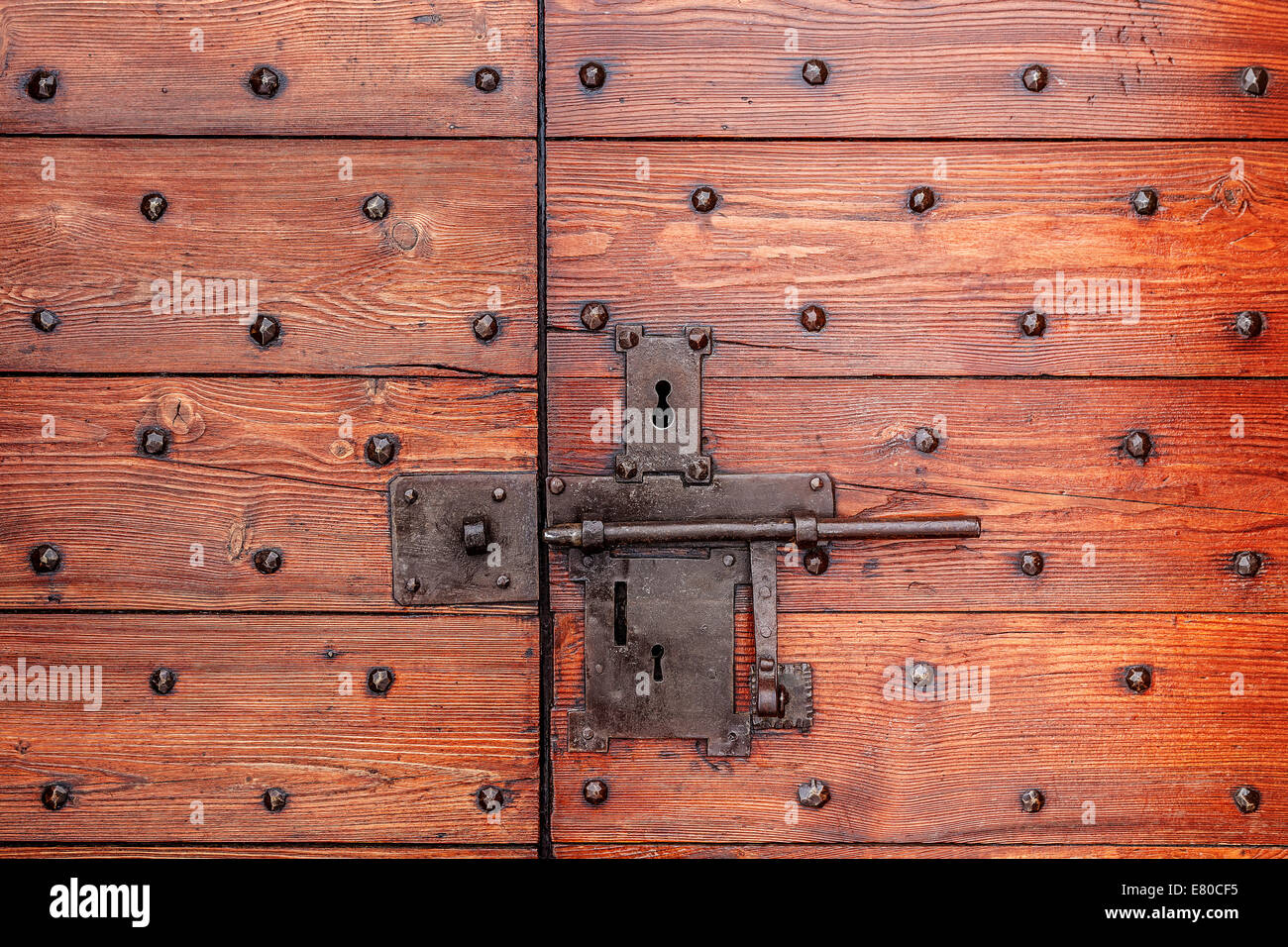 Old red wooden door with metal lock and bolt. - Stock Image