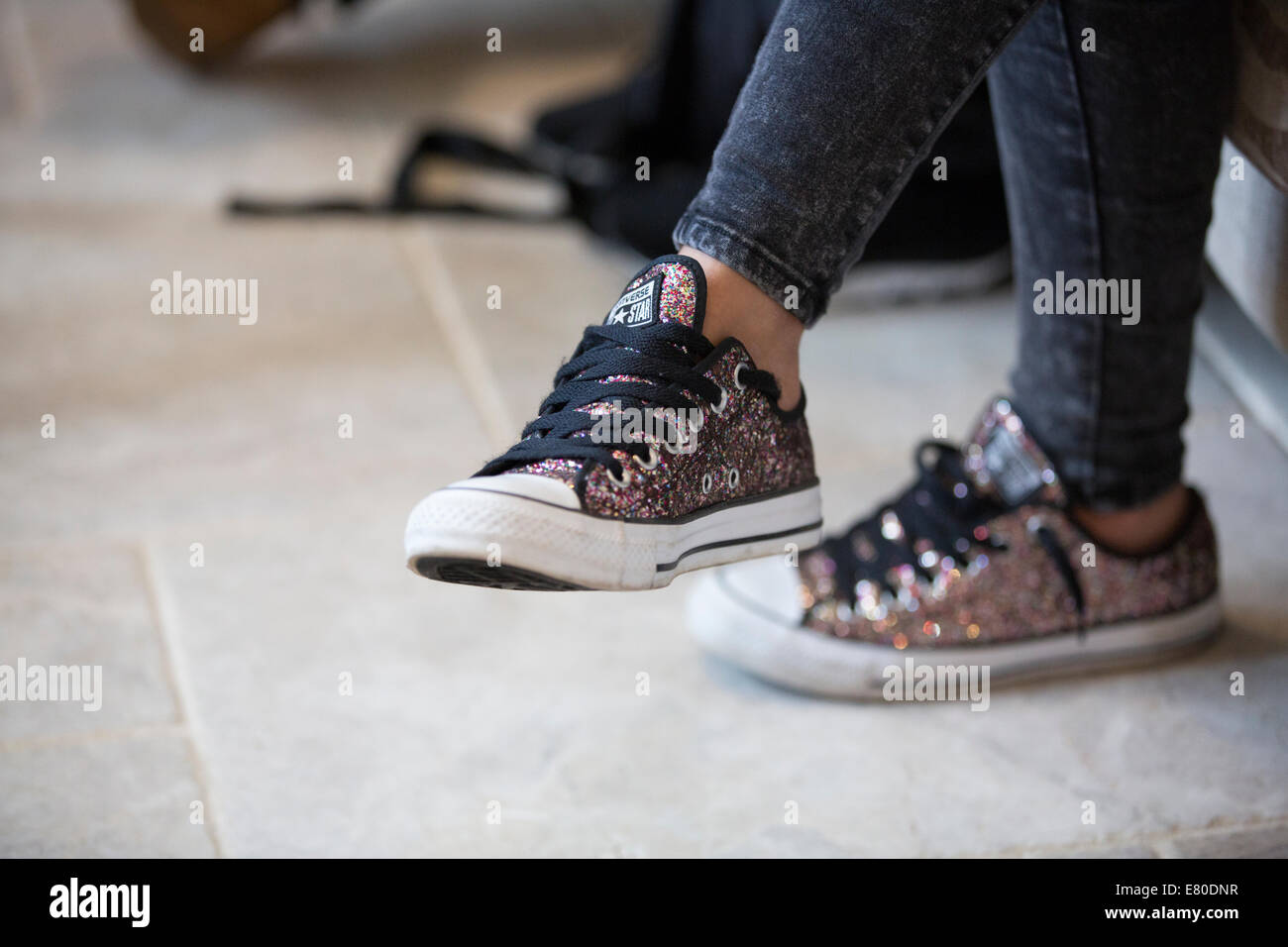 Young mother wearing Converse trainers - Stock Image
