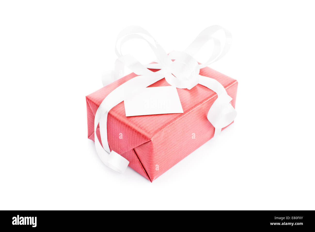 Close-up shot of a red gift box with white ribbons and a greetings card attached to it isolated on white background - Stock Image