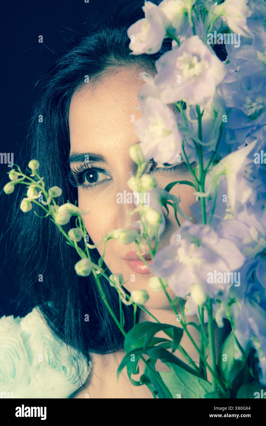 Woman holding flowers in front of her face - Stock Image