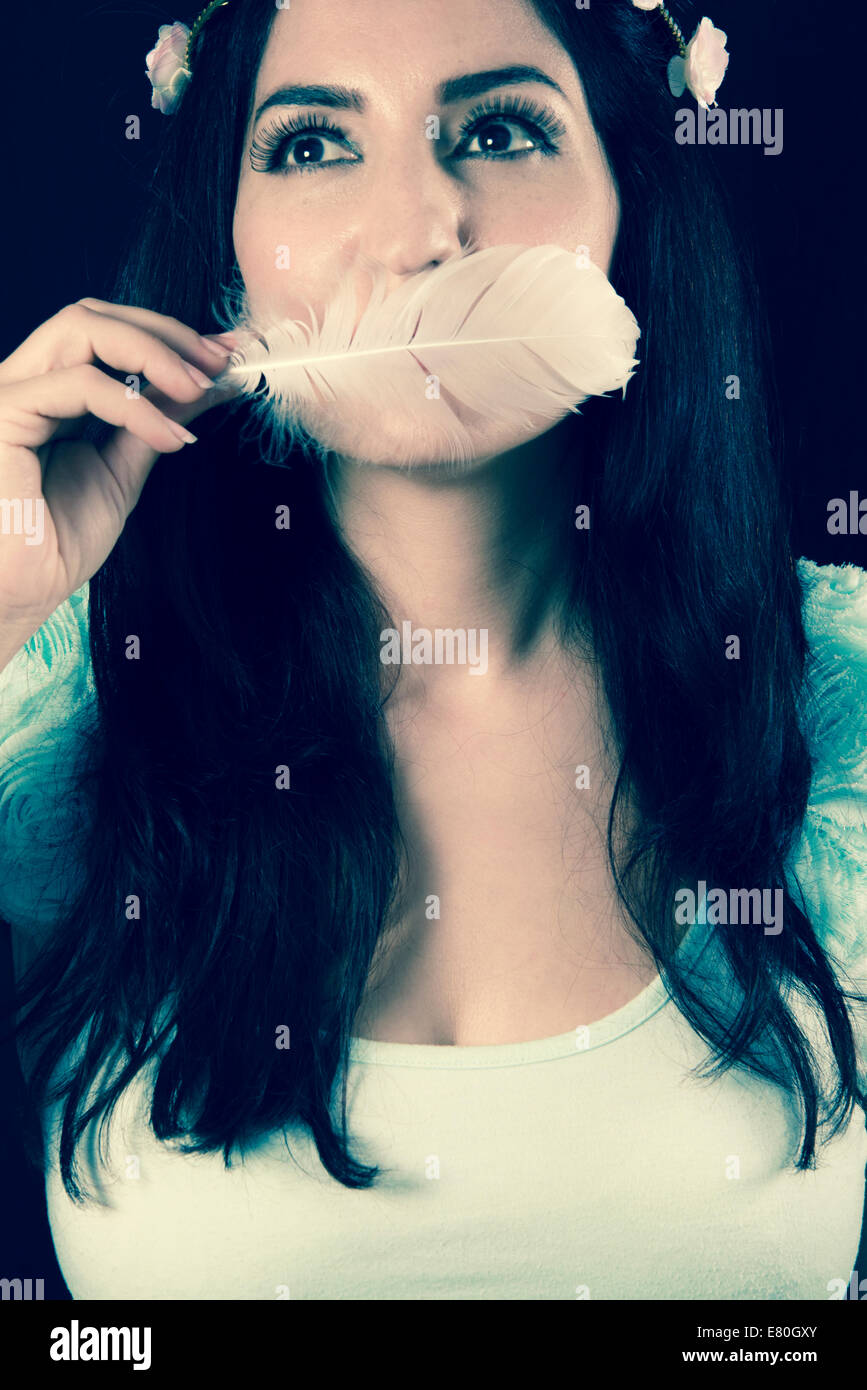 Woman holding a white feather in front of her mouth Stock Photo
