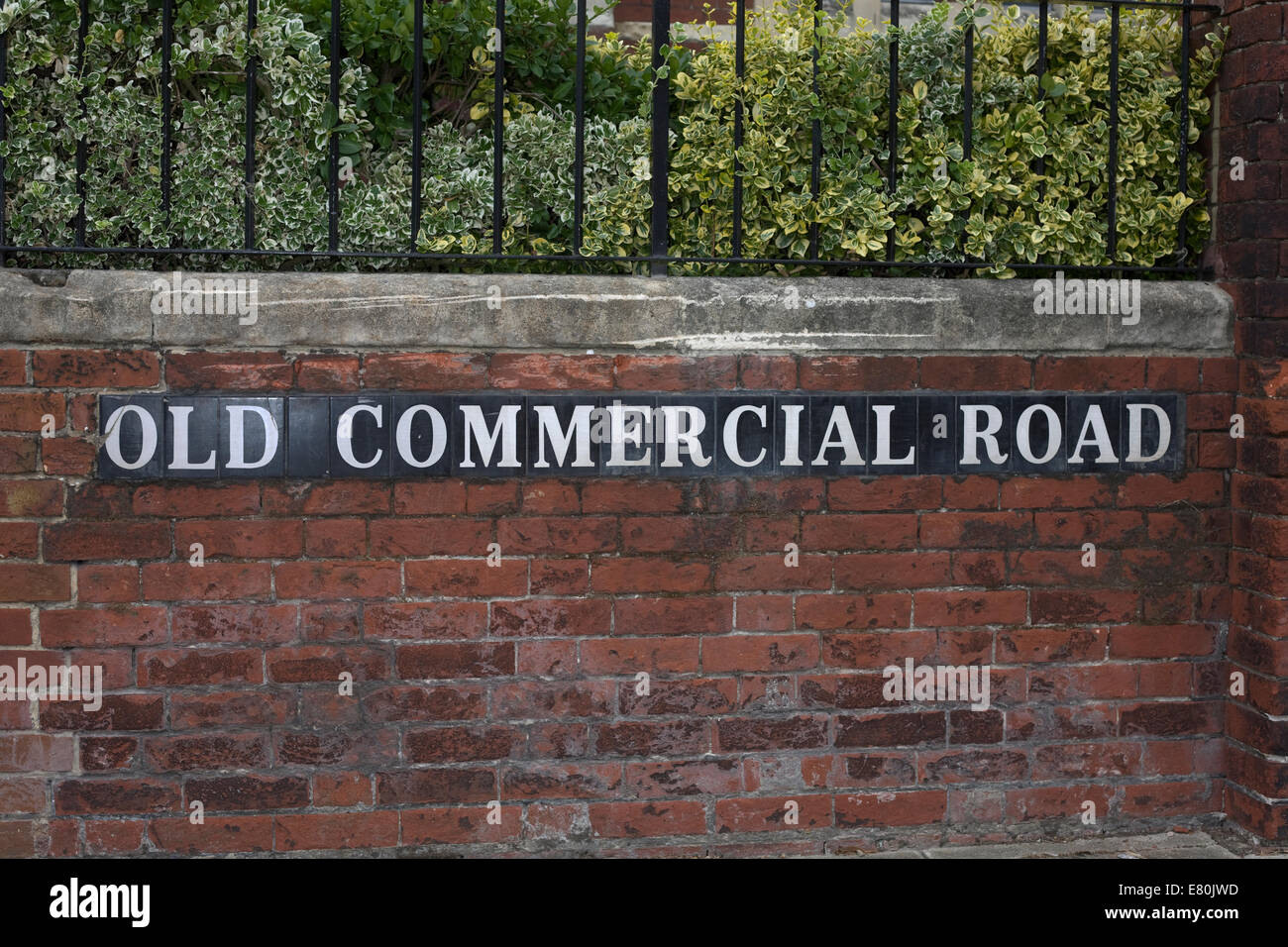 road name of Old Commercial Road set in brick wall with black metal railing above - Stock Image