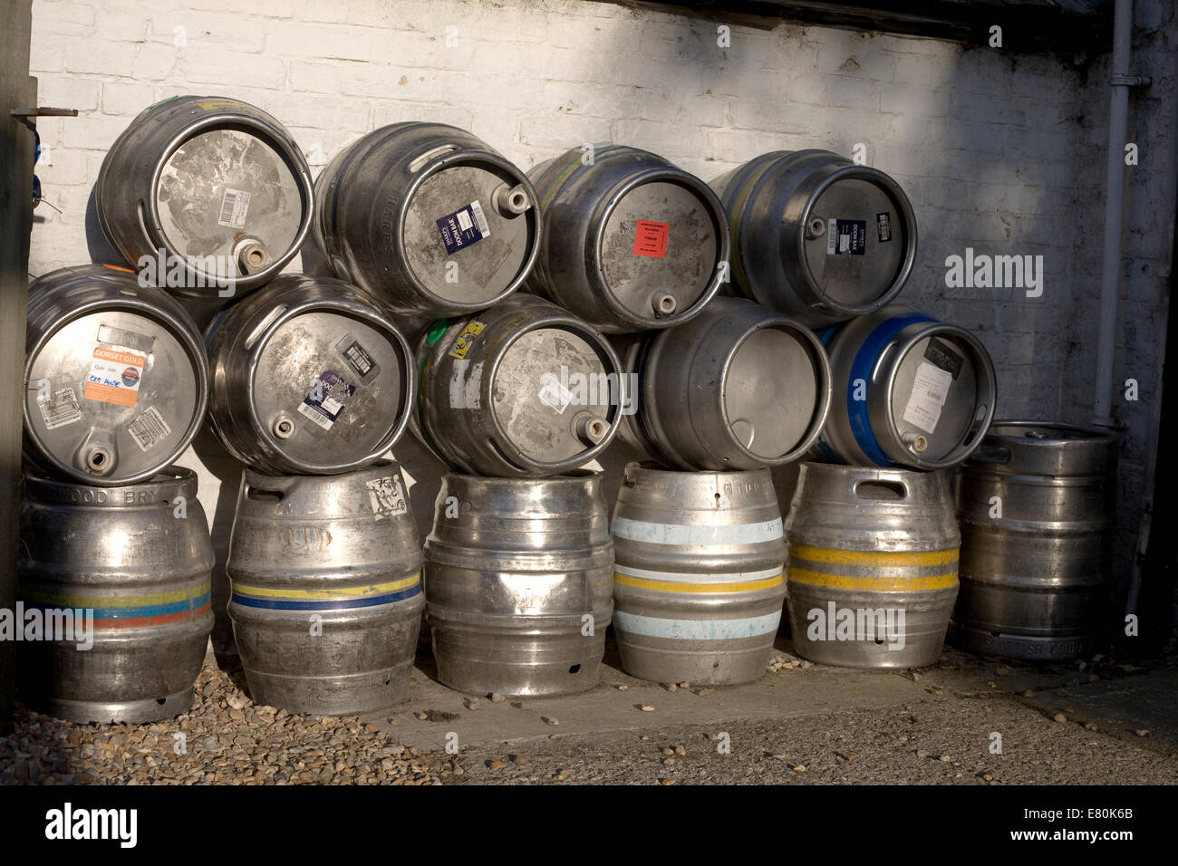 Pile of metal beer barrels outside the Old house at home in Chidham, Sussex on a summer evening - Stock Image