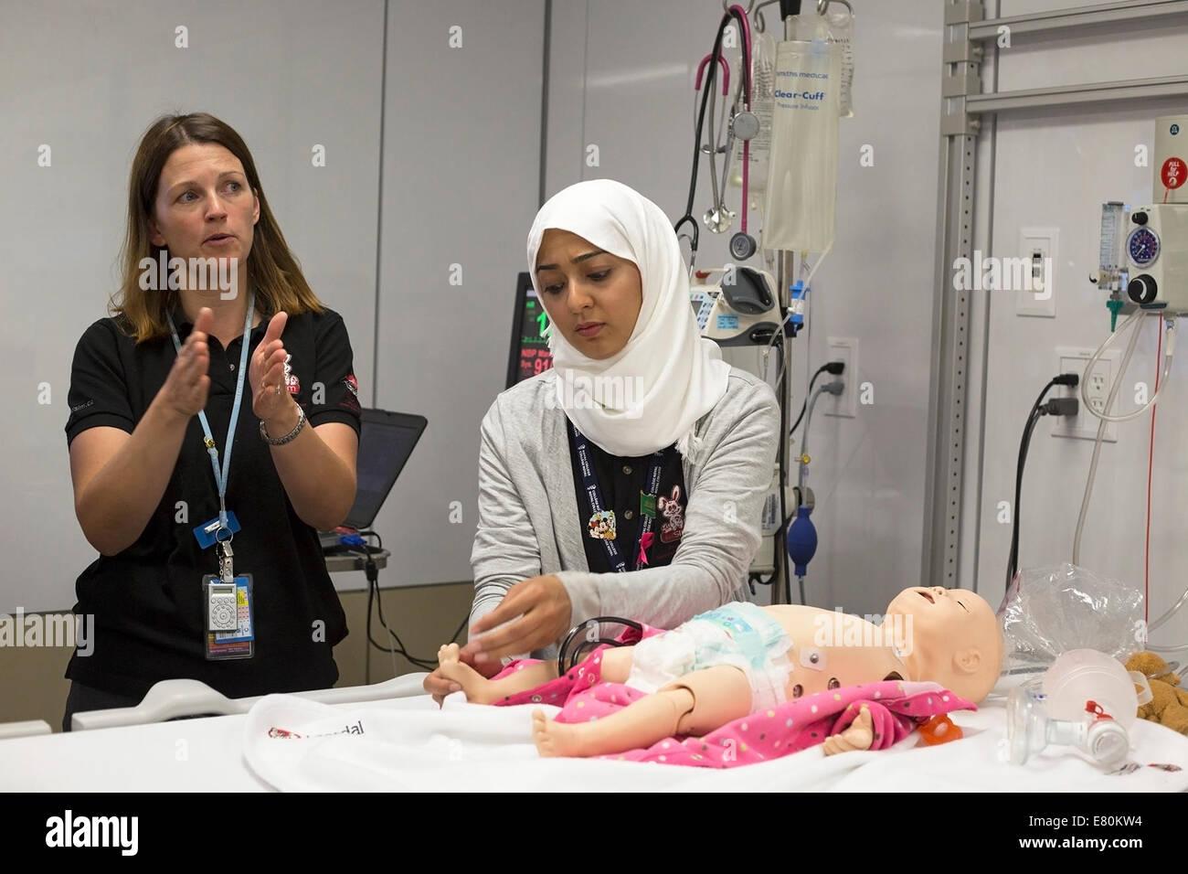 Calgary, Alberta, Canada, 27 Sep, 2014. Pediatric intensive care nurse Helen Catene (left) and pediatric doctor - Stock Image