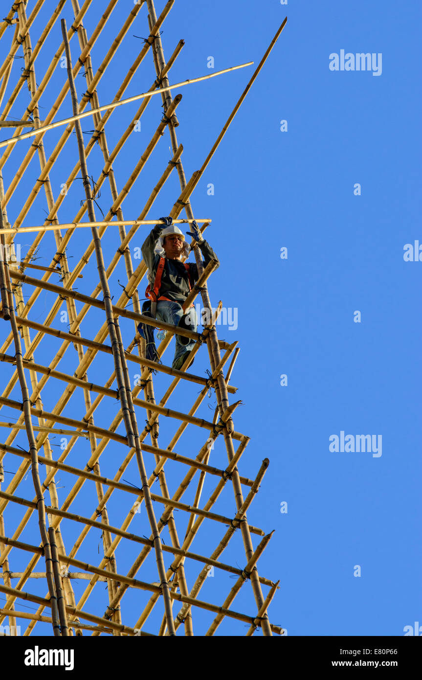 Chinese construction workers on bamboo scaffolding, Hong Kong, China. - Stock Image