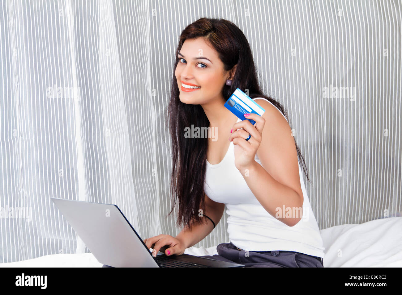 indian Beautiful Ladies online shopping with laptop - Stock Image