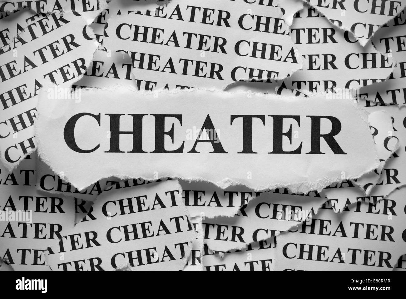 Torn pieces of paper with the word 'Cheater'. Black and White. Close-up. - Stock Image