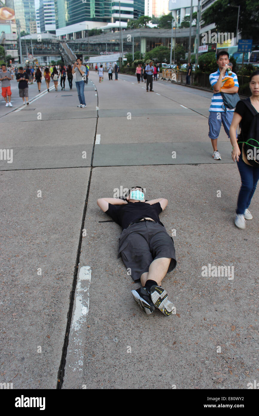 Hong Kong, 28 Sep, 2014. Hong Kong Protests: A Pro-democracy lies down in Queensway, a busy road in Hong Kong, at - Stock Image