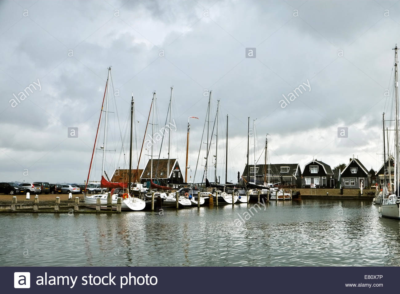 Sailboats and other watercraft in the harbor of Marken, shops and restaurants along Havenbuurt in background. - Stock Image