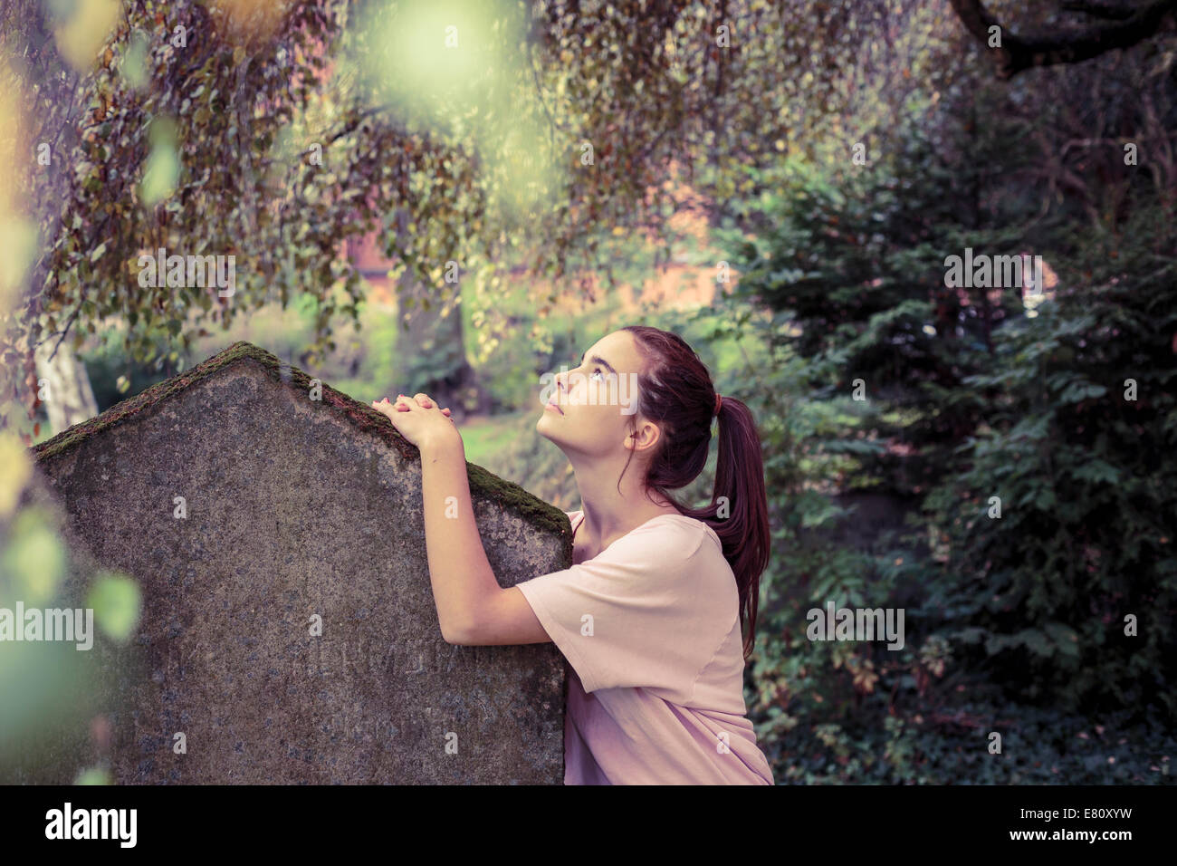 vintage shoot of a woman touching a moss overgrown tombstone - Stock Image