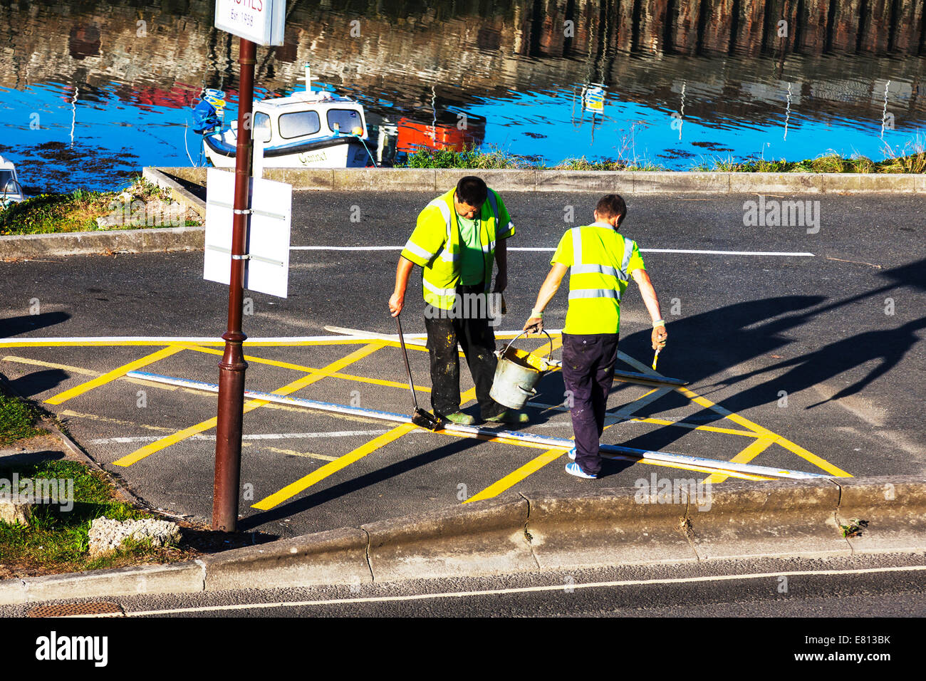 yellow line painting box junction two men working workers paint brush marks marking - Stock Image