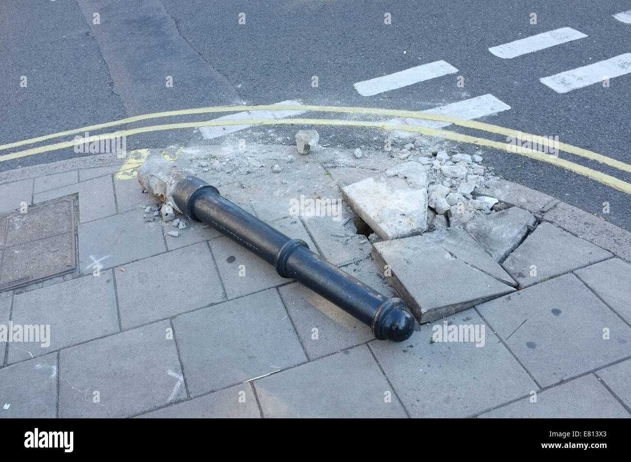 Street furniture damage with broken paving stones at road junction. - Stock Image