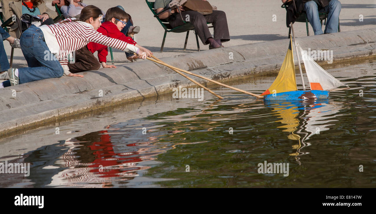 France, Paris, Children playing with toy sailboat, Tuileries Garden ...