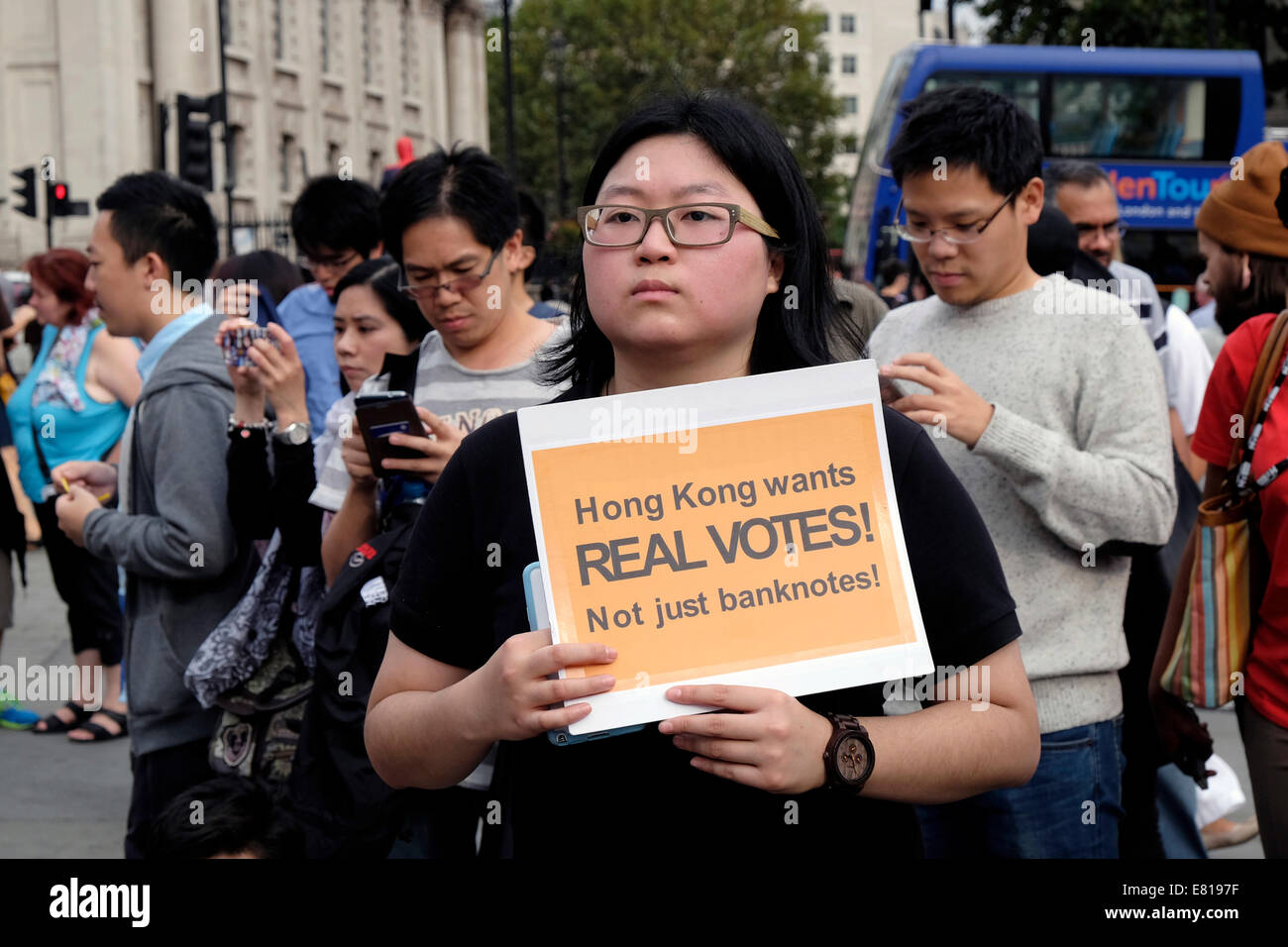 """A young woman from Hong Kong holds a placard reading """" Hong Kong wants real votes"""" Stock Photo"""