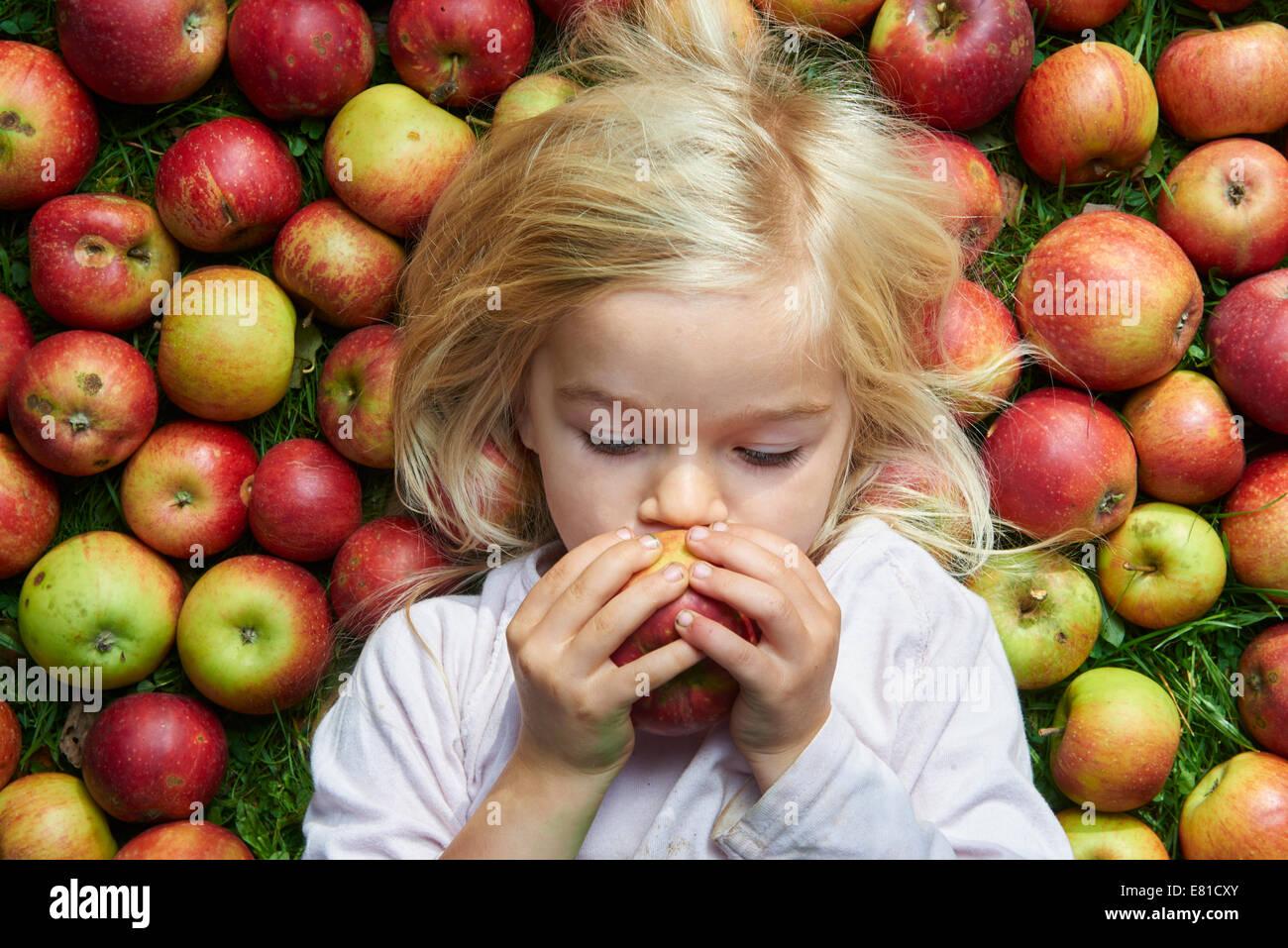 little girl lying on the grass eating green red apples Stock Photo