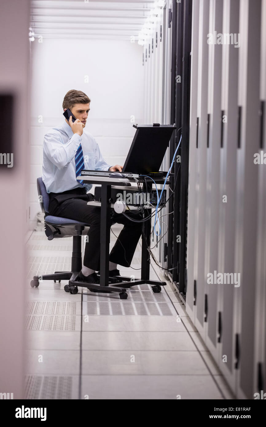Technician talking on phone while diagnosing servers - Stock Image