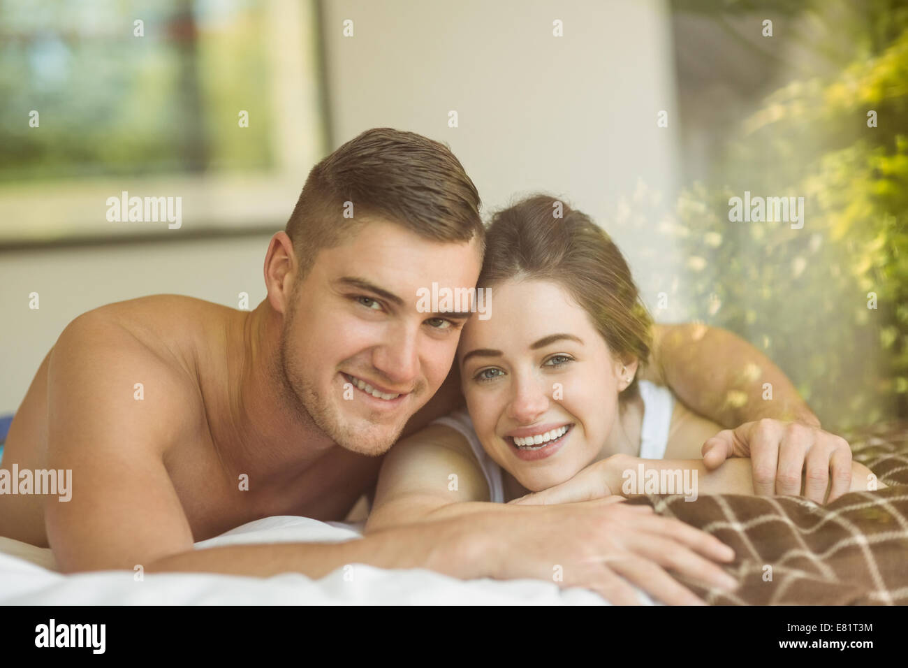 Cute couple lying on bed - Stock Image