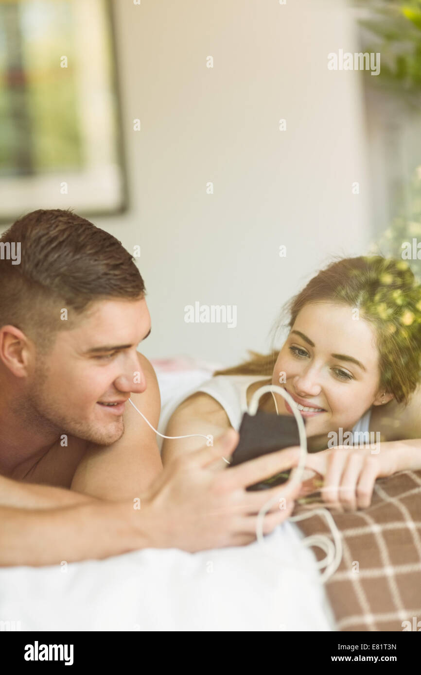 Cute couple lying on bed listening to music - Stock Image