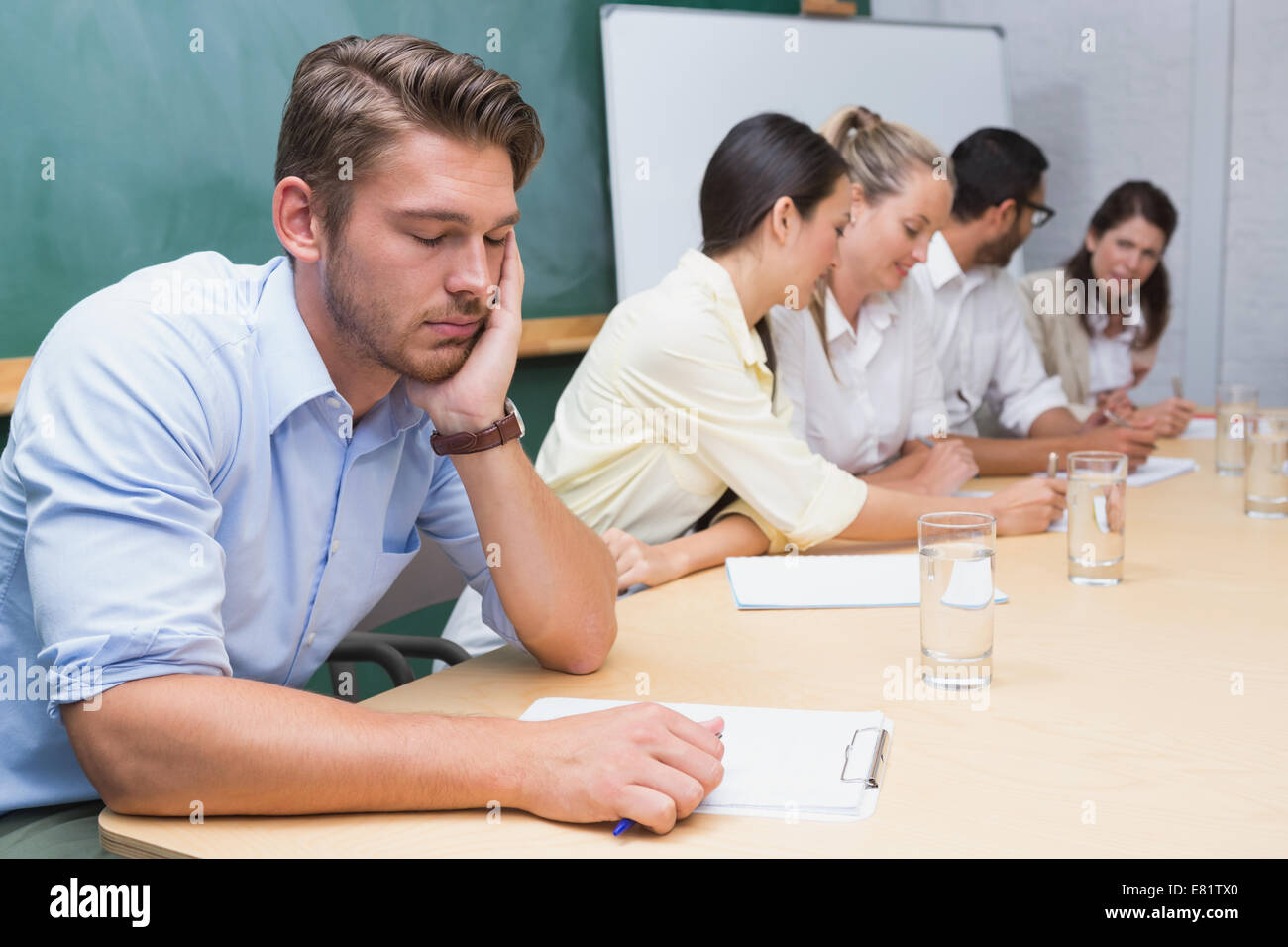 Buisness people working with man sleeping next to them - Stock Image