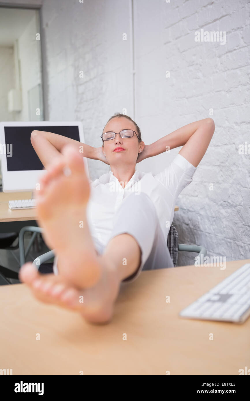 Businesswoman with legs crossed at ankle on desk - Stock Image