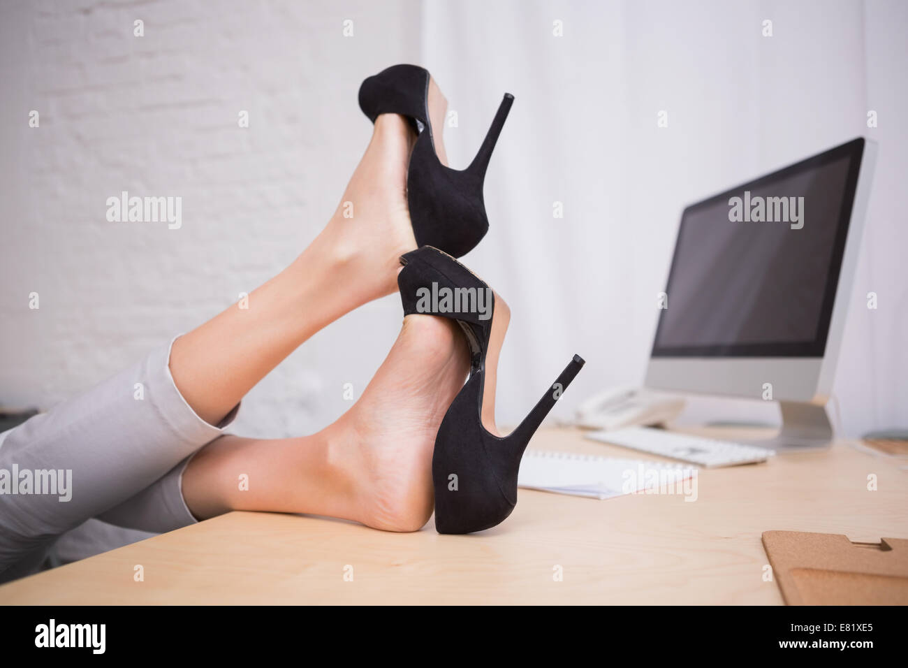Businesswoman with high heels on desk - Stock Image