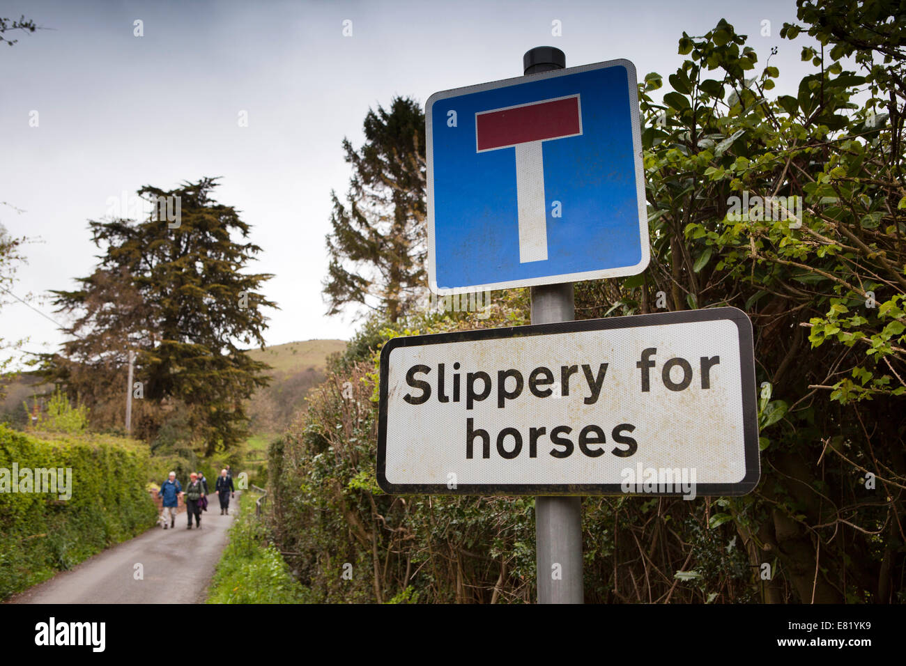 UK, England, Somerset, Bicknoller, Coleridge Way Walkers on path with Slippery for Horses sign - Stock Image