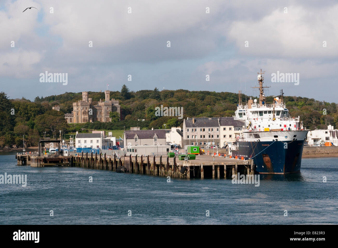 Stornoway Harbour with Lews Castle in background and the MV Pharos buoy laying vessel in port. - Stock Image