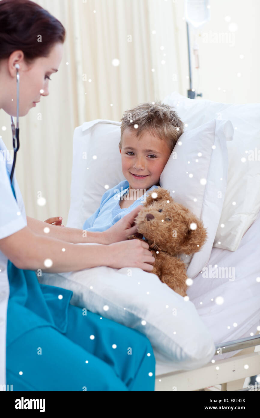 Female doctor listening to a child chest and a teddy bear - Stock Image