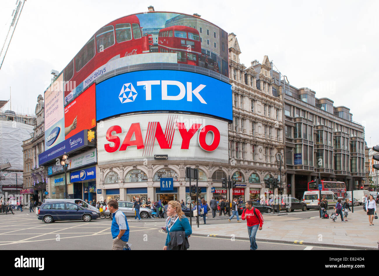 Tourists walk by Piccadilly Circus in London - Stock Image
