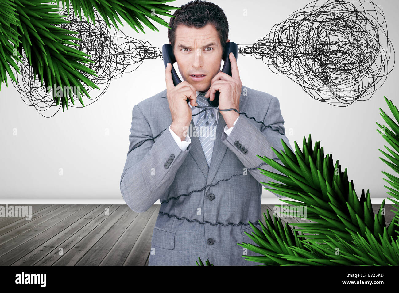 Overworked businessman holding two telephones - Stock Image