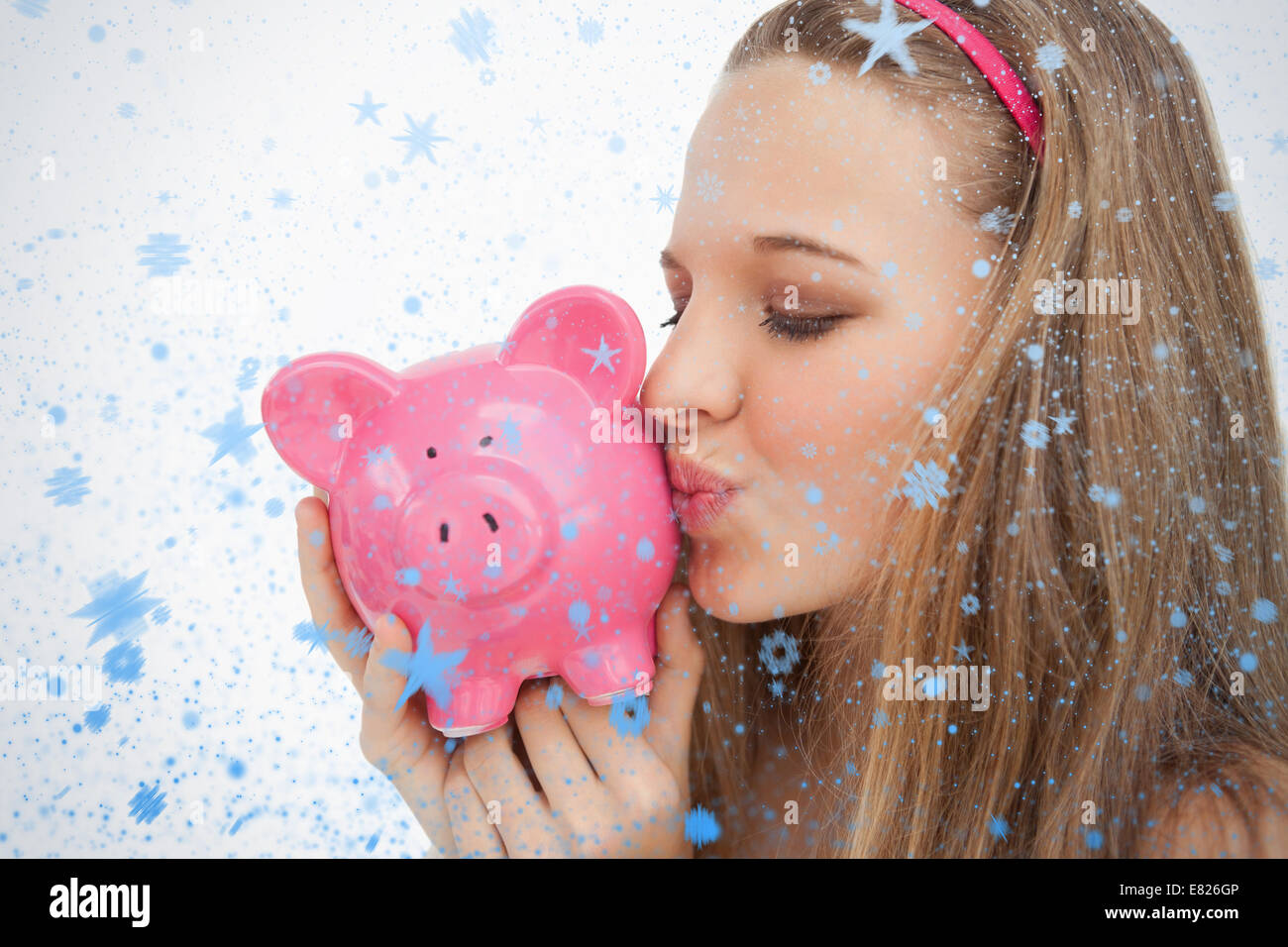 Close up of a young woman kissing a piggybank - Stock Image