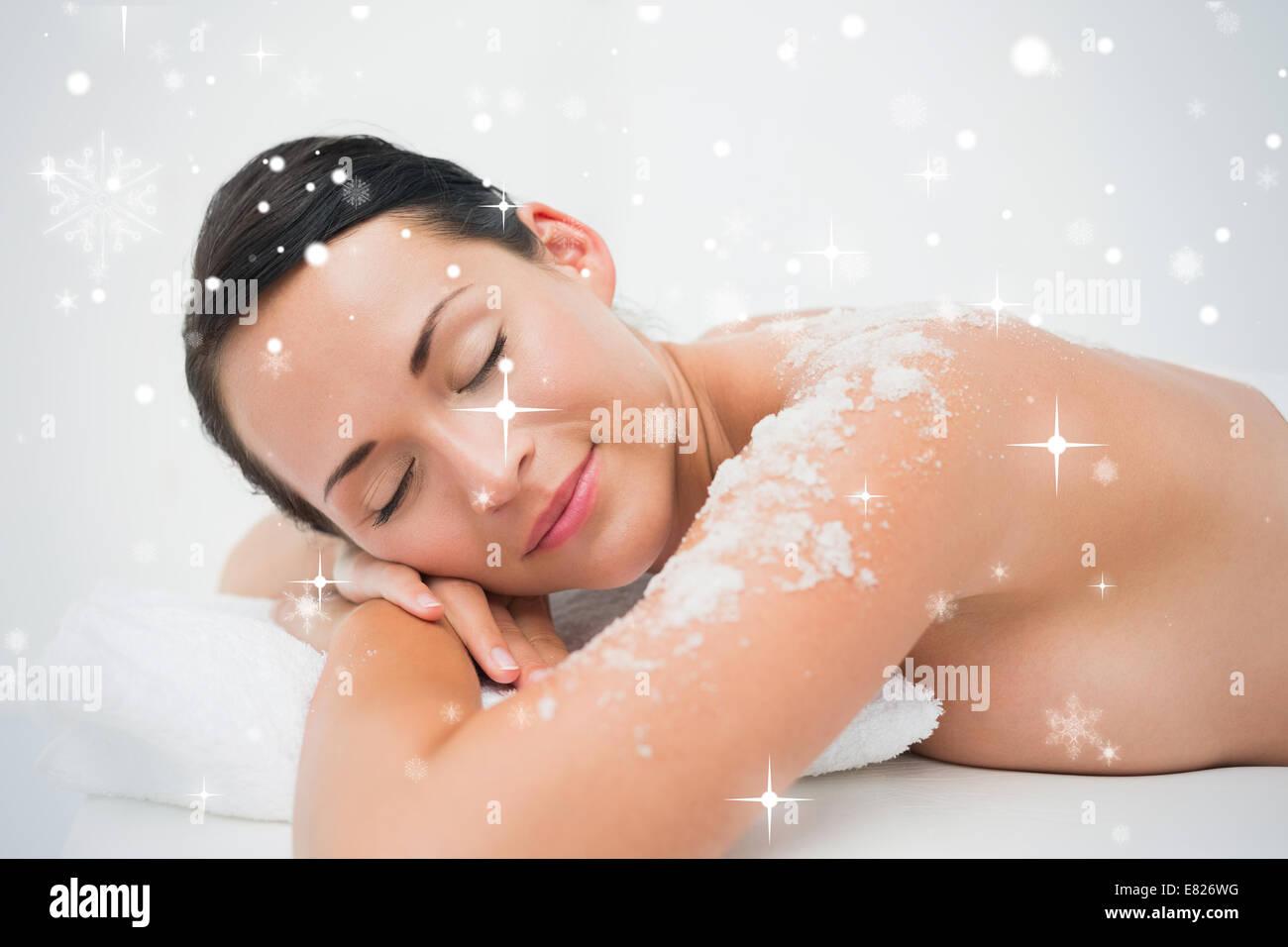 Peaceful brunette lying with salt scrub on shoulders - Stock Image