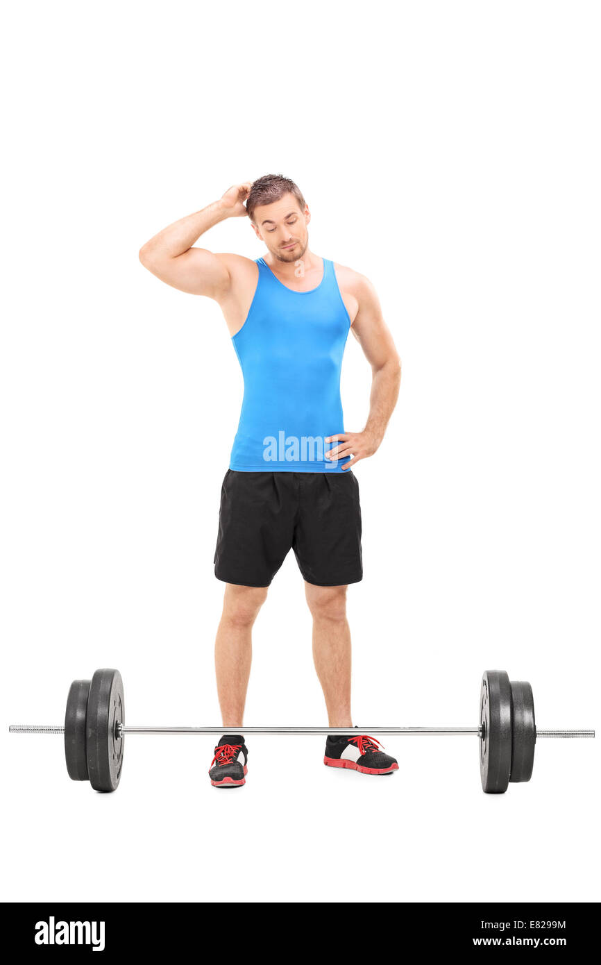 Full length portrait of a doubtful male athlete looking at a barbell isolated on white background - Stock Image
