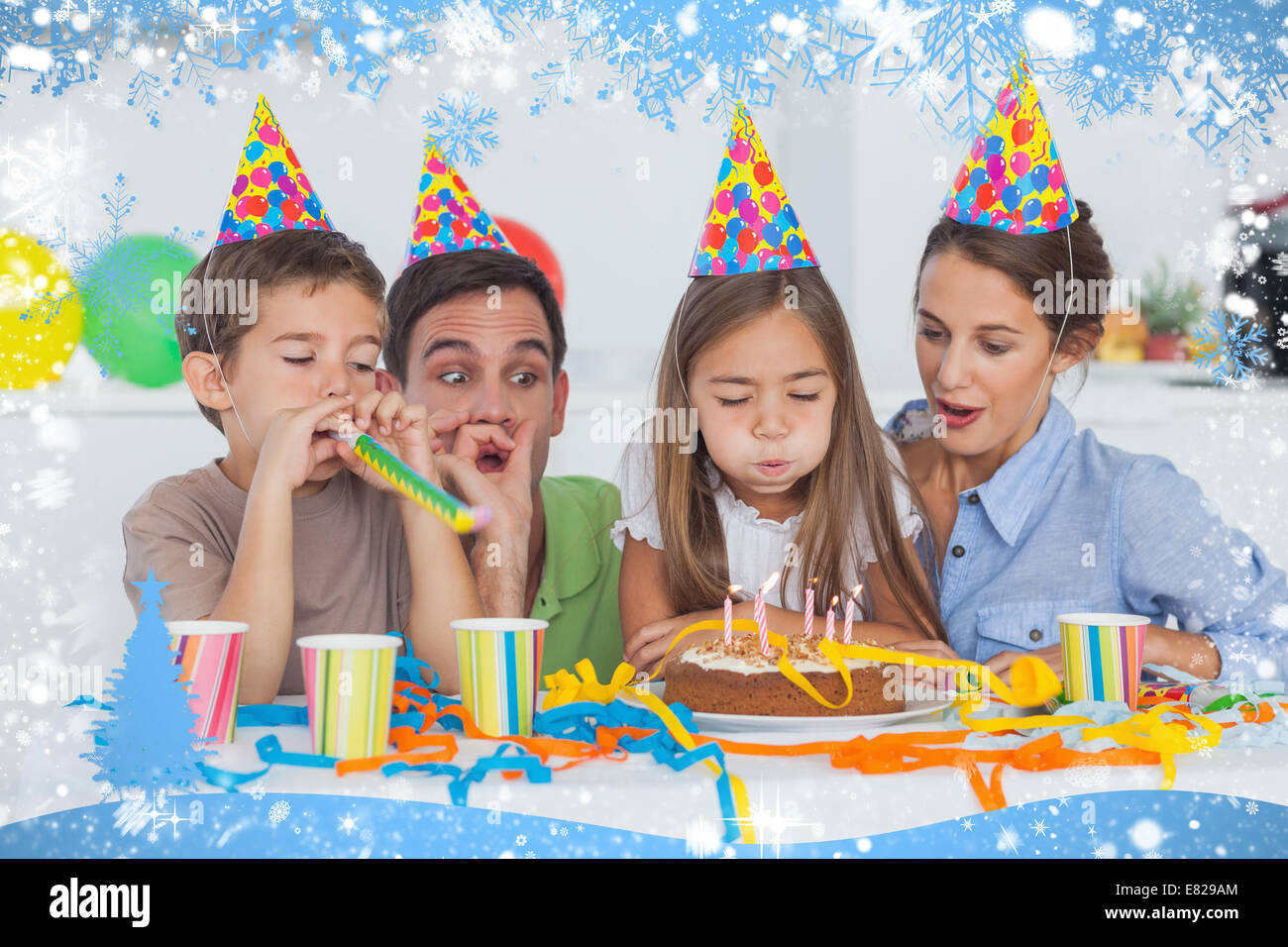 Little girl blowing her candles during her birthday party - Stock Image
