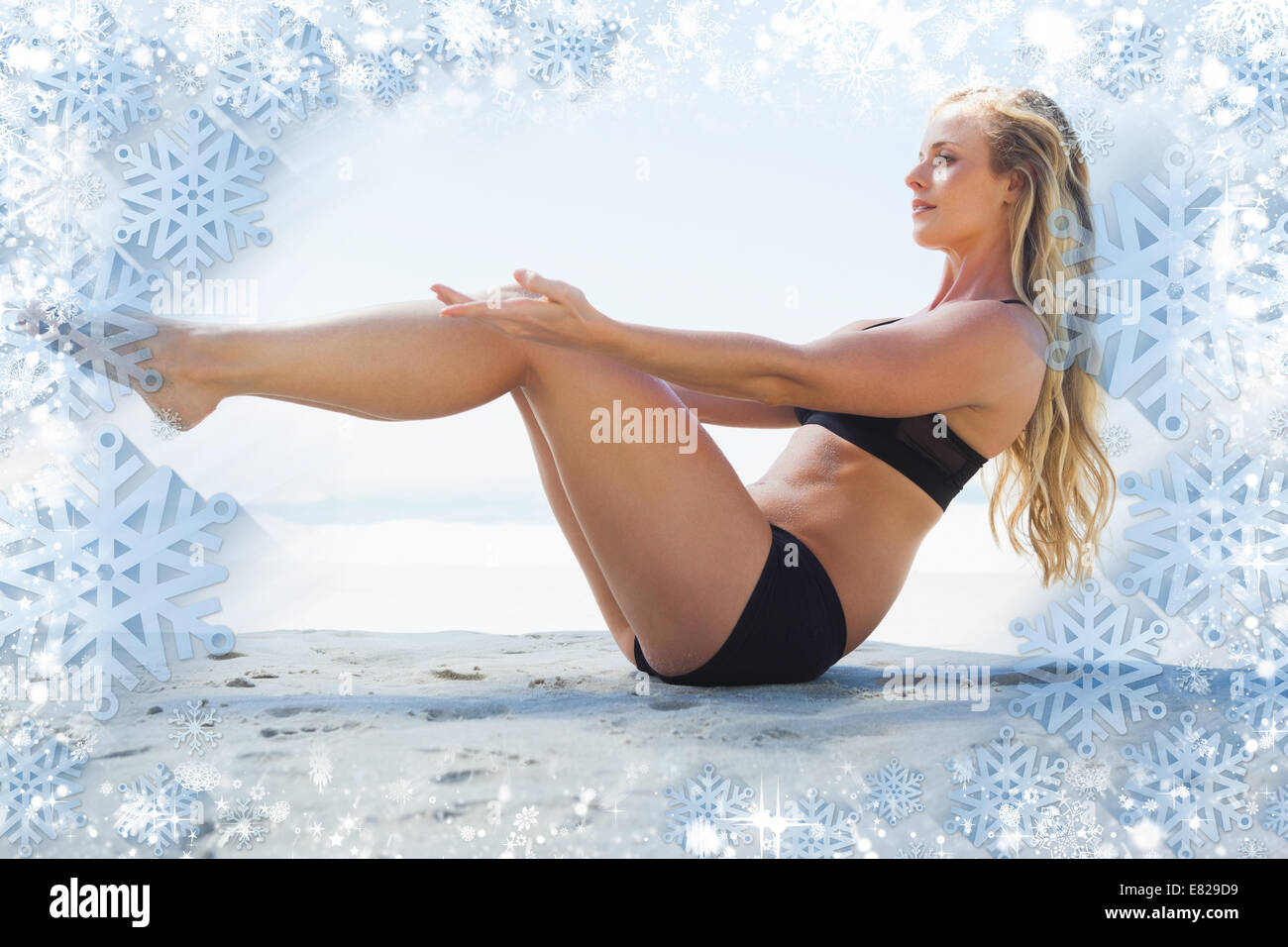 Fit blonde in core balance pilates pose on the beach - Stock Image