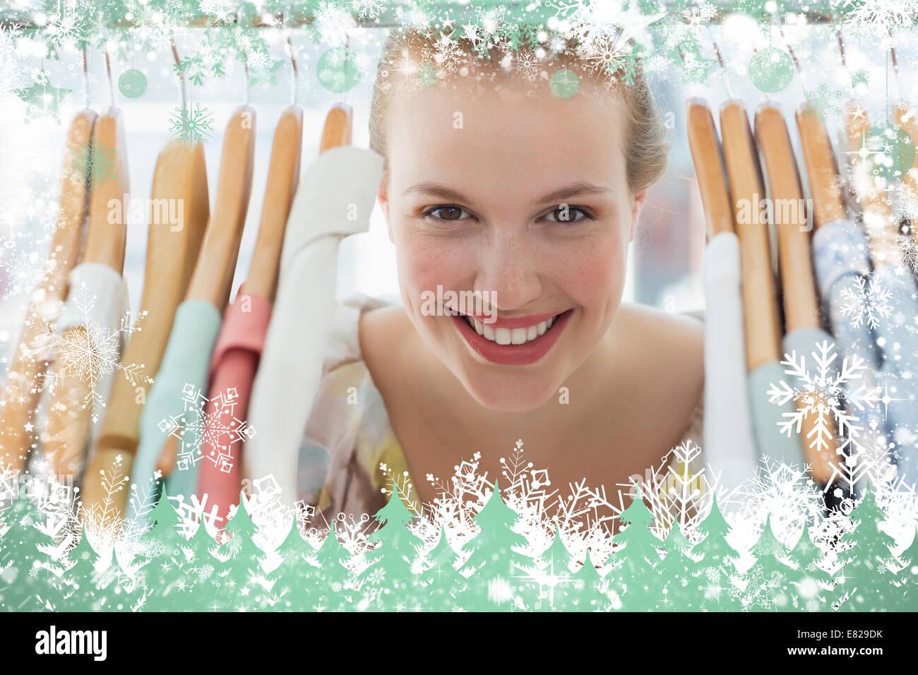 Happy female customer amid clothes rack - Stock Image