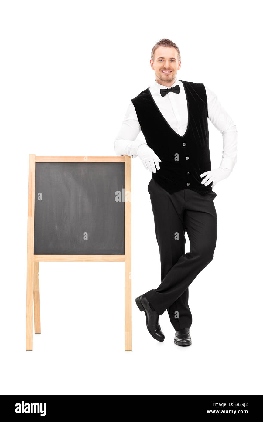 Full length portrait of a male waiter standing next to a blackboard isolated on white background - Stock Image