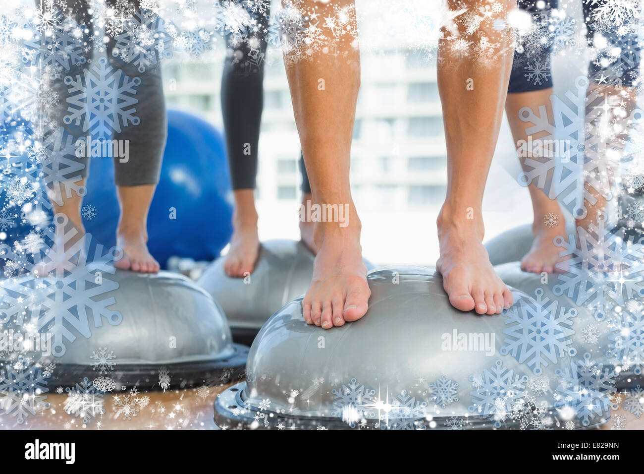 Low section of fit people standing on exercise equipment - Stock Image