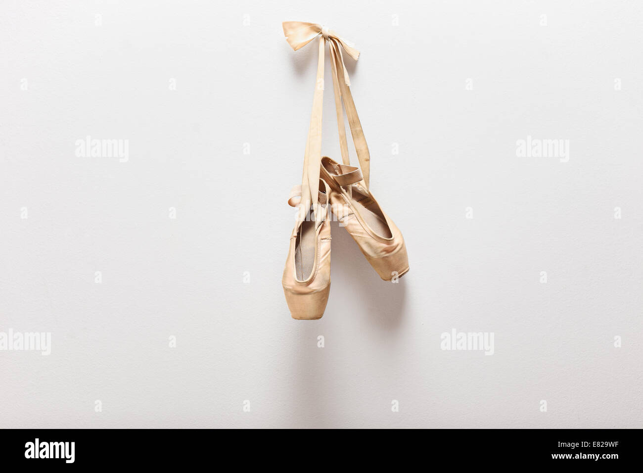 Pair of old silky ballet shoes hanging on a wall - Stock Image